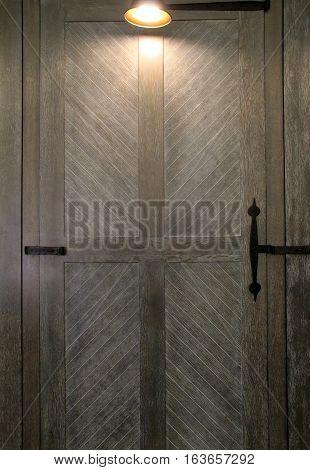 Vertical image of old wood door with black metal hardware and soft lighting overhead.