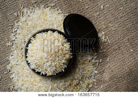 Rice in black wood container on the sack.