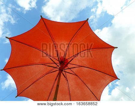 One red colored parasol against vivid blue sky and white cloud