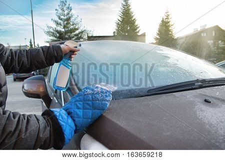 Man uses defroster spray to remove frost from the car windshield