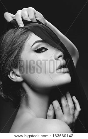 Portrait of beautiful young woman with cat eye make-up in black fabric. Studio beauty shot over black background. Monochrome.