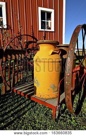 A vintage painted cream can rests on a two wheeled cart along side a red barn