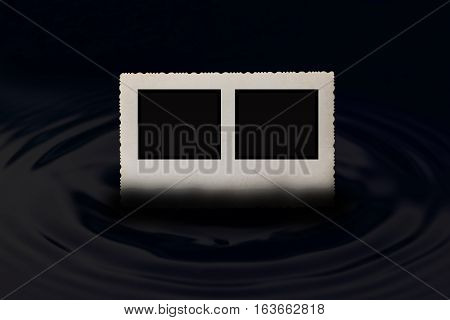 Front view of an old vintage photo frame with jagged edges horizontally partially submerged in the water which forms a circle wave in dark hues. Free place for your text is in two small black rectangles in the photo.