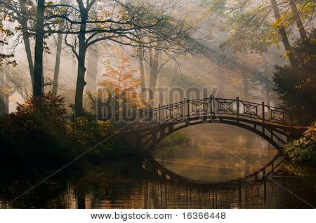 Old bridge in misty autumn park