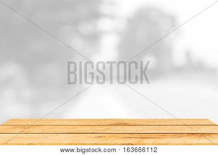 empty brown wooden table and interior blur background with bokeh image, for product display montage. Selected focus.