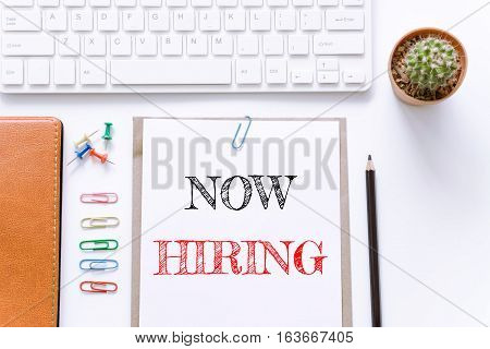 Text Now hiring on white paper background / business concept