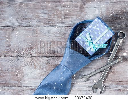 Father's day background on rustic wooden board with man's tie, wrenches and blue gift box. Copy space. Horizontal image