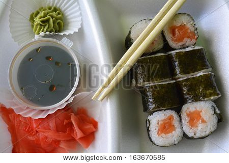 sushi rolls on plate with chopsticks, wasabi sauce and ginger