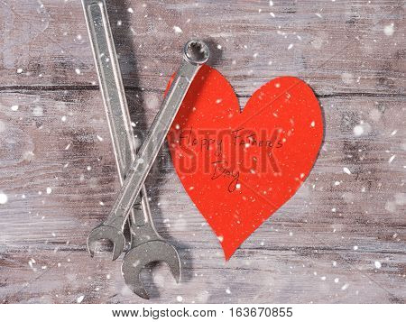 Father's day background on rustic wooden board with wrenches and a red paper heart with written Happy father's day. Falling snow