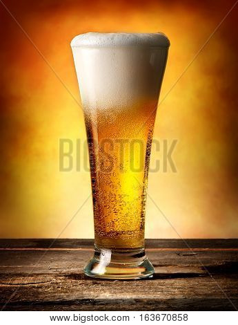 Glass of beer with bubbles on a wooden table