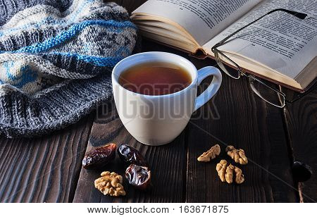 Cup of tea, book and knit cap on a wooden table