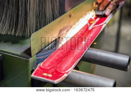 Person grinding skis. Hand of a worker maintaining skis in a grinding machine