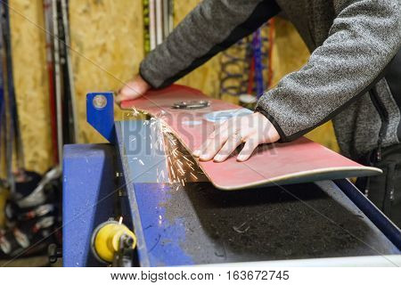 Maintenance of snowboard. Grinding and sparks. Ski service