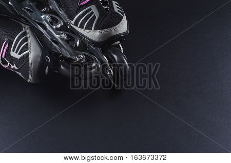 A pair of roller skates on a black background. Skating rollers stylish sports background.