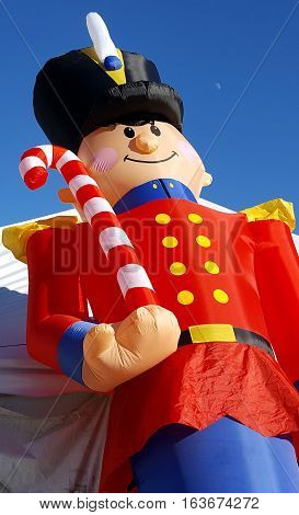 A huge inflatable toy soldier holds a Christmas candy cane welcoming shoppers to holiday sales