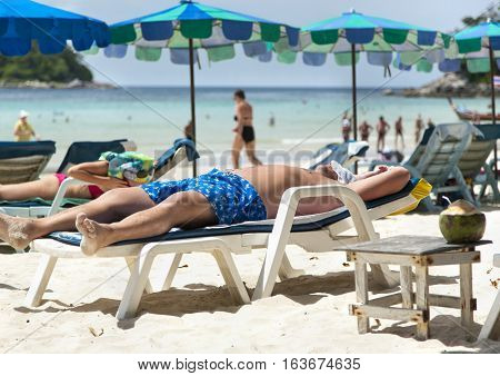Man relaxing on deck chair on a beach