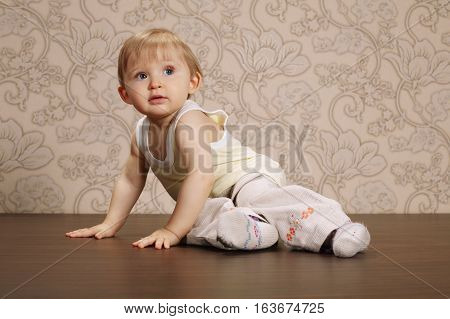 photo of beautiful funny child sitting on floor