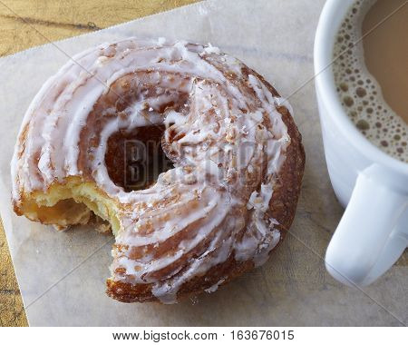 Glazed round cruller donut or doughnut on a piece of wax paper and beside a foamy cup of hot coffee in a white mug. The donut has a single bite removed.