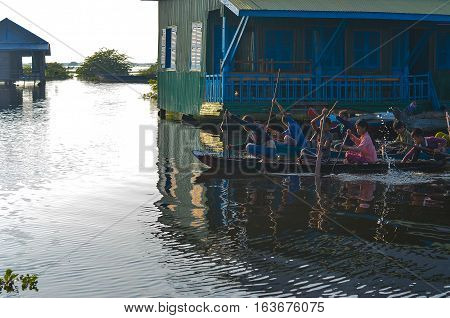 SIEM REAP CAMBODIA - November 2 2016: Child (boy and girl) playing on a boat in a floating village on the bank of Tonle Sap Lake. Tonle Sap is the largest freshwater lake in SE Asia peaking at 16k km2