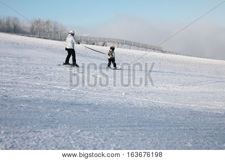Little skier on the slopes accompanied with a helmet on his head. Skier is tied to a safety rope. Suitable for promotional use instead of the headline.