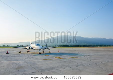 Small Airplane or Aeroplane Parked at Airport.Small Airplane Famous to use Private Airplane.Sunset Light and Mountain View.