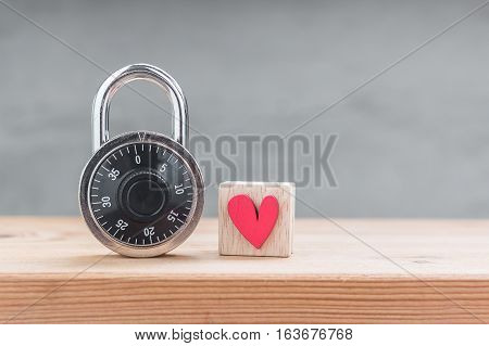 Red heart in wooden cube with combination padlock on wood table