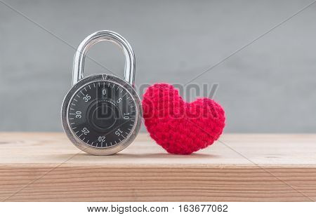 Red heart shape silk with combination padlock on wood table