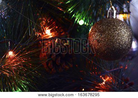 shiny Christmas ball, cones and sparkling colored lights garland on a Christmas tree