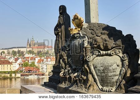 Baroque Statues on the Charles Bridge with beautiful Prague Castle and St. Vitus Cathedral background. Focused to statue