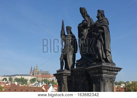 Baroque Statues on the Charles Bridge with beautiful Prague Castle and St. Vitus Cathedral background. Focused to Prague Castle