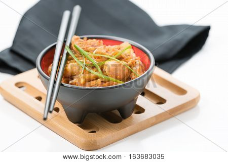 Bowl of delicious chicken pad thai on a bamboo trivet.