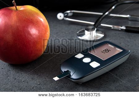 Blood glucose meter with interface created in graphic program and healthy food.