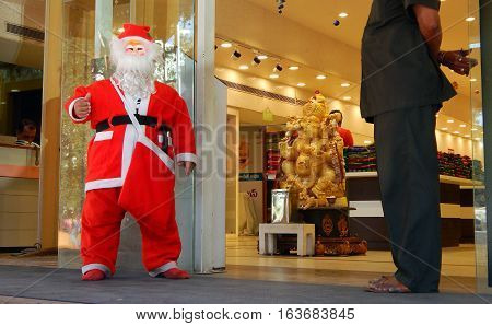 HYDERABAD,INDIA-DECEMBER 23:Man Dressed as Santa claus stand in front of clothes store wishing people during the season on December 23,2016 in Hyderabad,India
