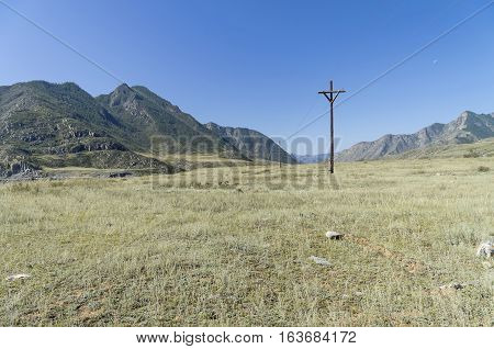 Small power line in the Altai mountains Russia. Sunny summer day.