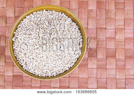 barley groats in a brown bowl, copy space