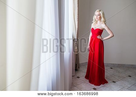 Beauty Brunette model woman in evening red dress. Beautiful fashion luxury makeup and hairstyle.