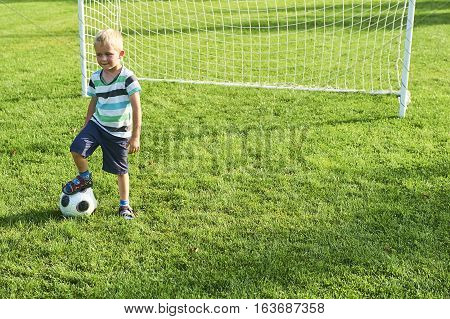 Cute little blond boy playing at being a goalkeeper on a sportsfield standing in the goalposts in sunny summer day