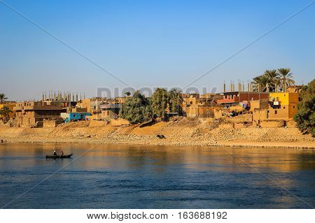 Nile River Egypt - February 3 2016: People on a boat with Village along the shore of the Nile River in Egypt Africa at sunset