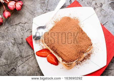 Tiramisu with strawberry on the table. Top view.