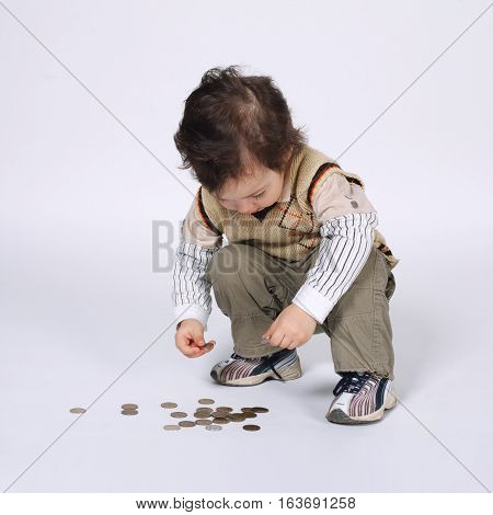 cute little boy plays with coins on bright background