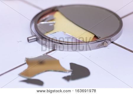 Destruction low self esteem accident conflict concept. Broken mirror lying on tiled floor