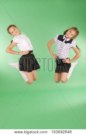 Cute happy school girls jumping. Isolated green background. Happiness friendship fashionable concept.