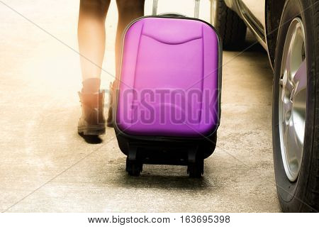 Person walk drag purple travel bag beside black car for travel and sun light