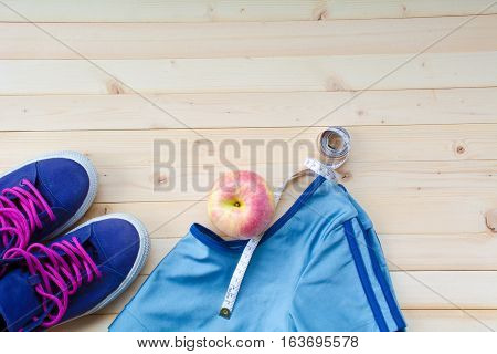 Exercise equipment sport shoes, sport shirt, apple and white tape measure for exercise and healthy on wood table top view