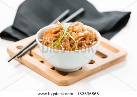 Spicy pad thai in a white bowl on a bamboo trivet.