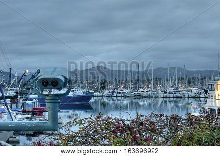 Ventura Harbor under overcast sky behind tourist telescope. poster
