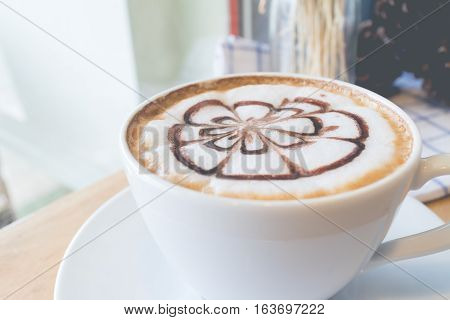 Hot coffee with foam milk art in afternoon break. Coffee mocha on the wood desk.(selective focus vintage effect)