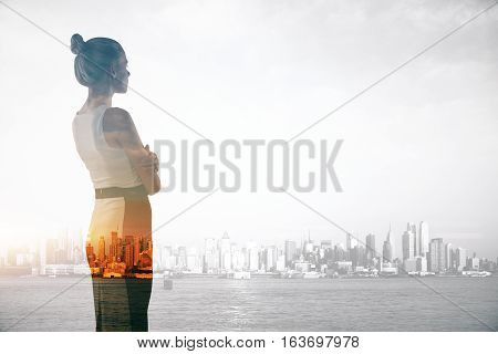 Attractive young businesswoman on abstract city background with copy space. Double exposure. Research concept