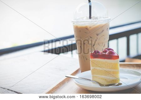Sponge cake with cherry syrup. Peace of cherry cake serve with iced coffee in cozy outdoor cafe.