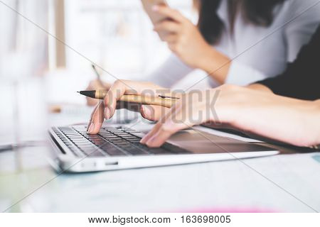 Side view of female hands using laptop computer placed on messy office desktop